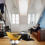zona living di un attico a Parigi con materiali grezzi